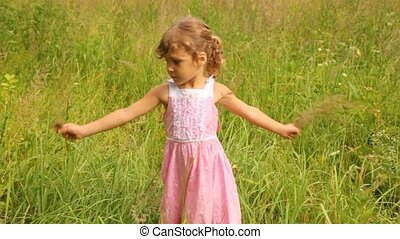 girl is turning round holding the blades of grass in hands -...