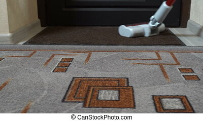 Girl is vacuuming a room - The girl cleans the carpet in the...