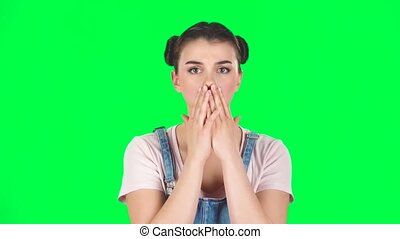 Girl is very surprised and upset on green screen at studio, slow motion. Girl with two hair-buns, wearing denim overalls and pink t-shirt.