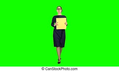Girl is walking along the street with a folder in her hands. Green screen