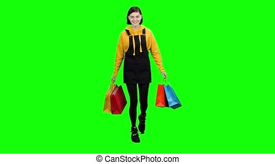 Girl is walking along the street with packages in her hands. Green screen