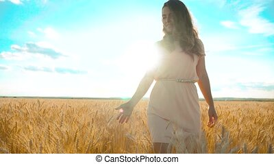girl is walking along the wheat field nature slow motion...
