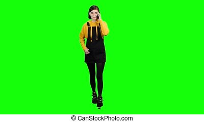 Girl is walking down the street and talking on the phone. Green screen