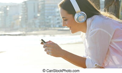 Girl is watching and listening media on a smart phone - Side...