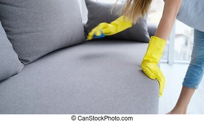 Girl is wiping sofa with sponge - Girl in yellow rubber ...