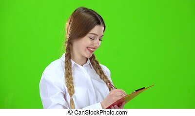 Girl is writing on a white tablet. Green screen