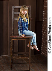 Girl jeans and blue shirt is sitting on a high chair in room with brown walls