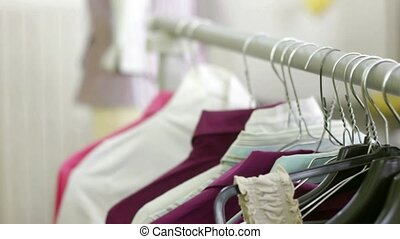 Young hispanic female dressmaker adjusting clothes on tailoring mannequin and smiling at camera. Dolly shot