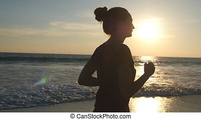 Girl jogging along ocean shore during sunrise. Silhouette of young woman running on sea beach at sunset. Female sportsman exercising outdoor. Healthy active workout lifestyle at nature. Slow motion
