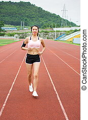 Girl jogging on a running track