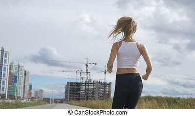 Girl jogging on the background of houses