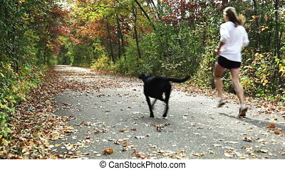 Girl jogging with dog on trail. - Young girl jogging with...