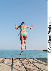 Girl jump into the water from the pier