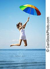 Girl jump  with a rainbow umbrella
