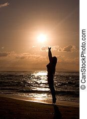 Girl jumping at beach on sunrise