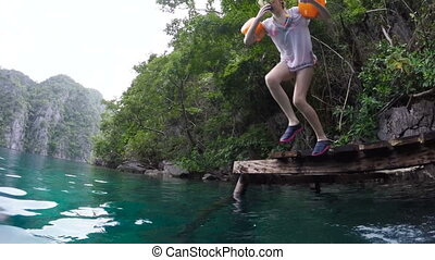 Girl jumping into the lake.