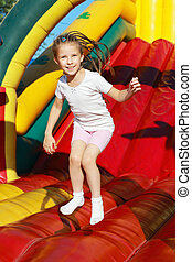 Girl jumping on a trampoline  -  Funky fun in a summer park
