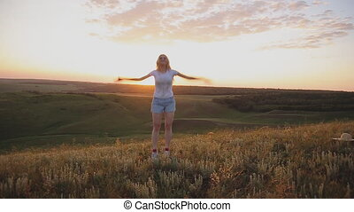 girl jumping on the background of sunset. outdoors