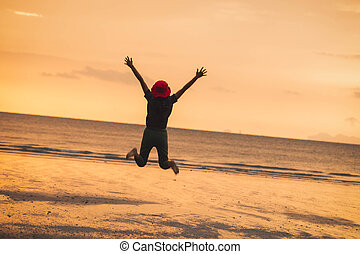 Girl jumping on the beach, at sunset.