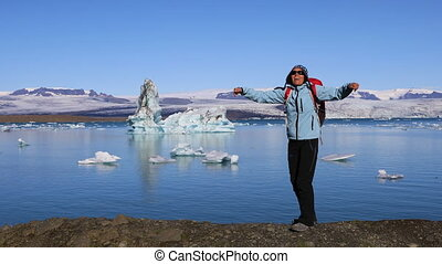 Girl jumping on the coast of the glacial lake Jokulsarlon -...