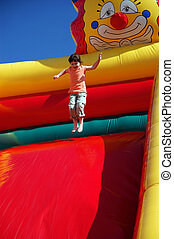 Girl jumping on the colored inflatable slide