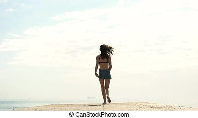 girl jumping on the pier at the sea
