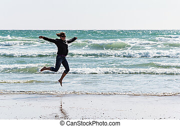 Girl jumping on the shore, Atlantic Ocean. Brittany, France.