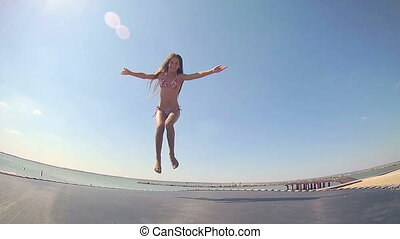 Young girl jumping on trampoline against blue sky