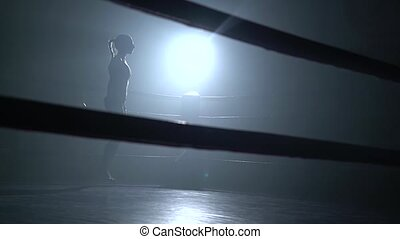Girl jumping rope in a dark ring . Silhouette - Girl jumping...
