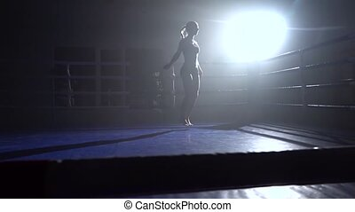 Girl jumping rope in a dark room . Silhouette. Slow motion -...