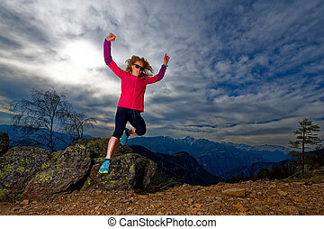 Girl jumps from rocks in the mountains during a workout
