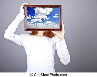 Girl keep frame with clouds sky inside. Studio shot.