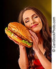 Girl keeps big sandwich.