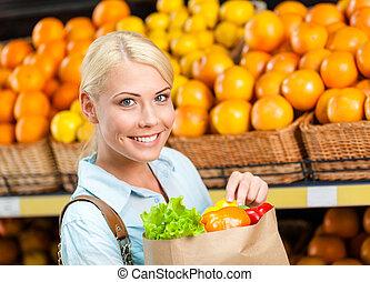 Girl keeps paper bag with fresh vegetables