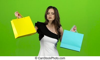 Girl keeps the shopping bags and doubts what to choose. Green screen. Slow motion