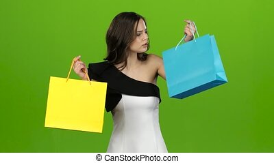 Girl keeps the shopping bags and doubts what to choose. Green screen