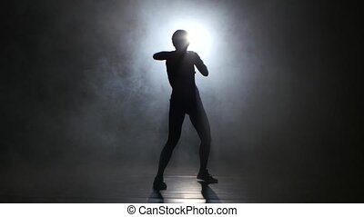 Girl kickboxer gloves sends the punches. Silhouette. Black background. Lights rear