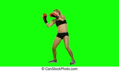 Girl kickboxer in a special form of training for competitions. Green screen. Side view
