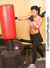 Attractive young woman training kickboxing using red punching bag
