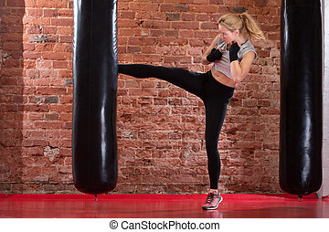 Girl kicking at punching bag - fit boxing girl kicking at...