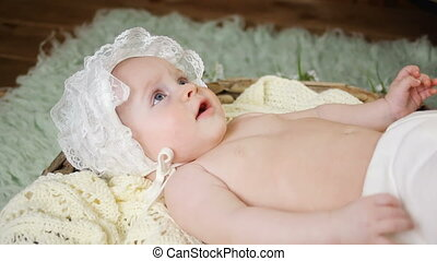 girl kid naked in a white cap lying in the basket