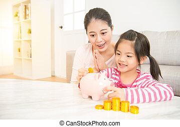 girl kid putting money into piggy bank