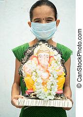 Girl Kid with medical mask holding Ganesha Idol on isolated background - concept of vinayaka Chaturthi festival celebrations during coronavirus or covid-19 pandemic.