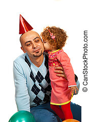 Girl kissing father at party