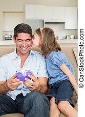 Girl kissing father holding gift box on sofa