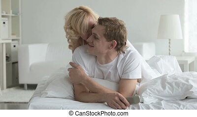 Smiling girl playfully kissing guy in bed