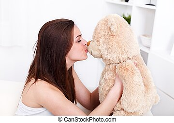 Girl kissing her teddy bear - Young woman sitting in sofa...