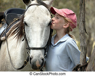 girl kissing horse - young girl rider kissing a white horse