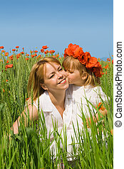 Little girl with poppy wreath kissing her mother on the green field full of poppies