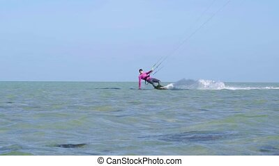 Girl Kite Surfing In Slow Motion - Kitesurfer jumps and...